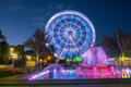 City Ferris wheel with a fountain in the evening in the Park