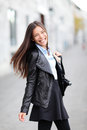City girl modern urban woman smiling happy from the heart female fashion wearing black leather jacket walking outside in street Stock Photo