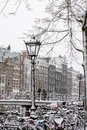 City lantern with many bikes in snow in winter in Amsterdam Royalty Free Stock Photo
