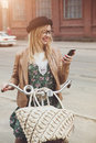 City lifestyle stylish hipster girl with bike using a phone text Royalty Free Stock Photo