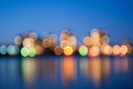 City lights blurred with bokeh effect reflected on water Stock Image