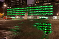 City lights urban abstract green of a multi storey car park with reflections on water after the rain at night in rotterdam Royalty Free Stock Photos