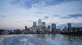 City of london skyline as seen from the thames color with ferry wake in foreground and multitinted blue and gray clouds overhead Royalty Free Stock Image