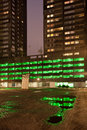 City at night urban abstract green lights of a multi storey car park with reflections on water after the rain in rotterdam holland Royalty Free Stock Photo
