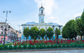 The city park chernivtsi ukraine june green trees and scenic flower beds with red roses located on foreground of town hall on Royalty Free Stock Images