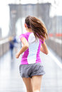 City runner woman running on brooklyn bridge rear view backside close up of female athlete training outside in rain in new york Royalty Free Stock Images