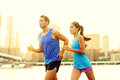 City running couple jogging outside runners training outdoors working out in brooklyn with manhattan new york in the Stock Image