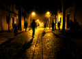 City street at night ​​at shadows of people walking down the Stock Photography