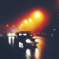 City street at night in fog cars and lighting poles Royalty Free Stock Image