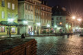 City street at night scenic view of old buildings in with silhouetted people walking on cobbled road Royalty Free Stock Photography