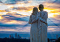 City sunrise watchers a view of a monument with a sculpture of a couple looking over the of atlanta as the sun tries to rise over Stock Images