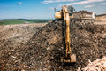 city waste dumping grounds with excavator loading trucks Royalty Free Stock Photo