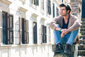 City young handsome man. Urban sitting model. Building windows Royalty Free Stock Photo