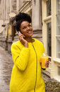 Citylife young woman on the phone holding a soft drink Royalty Free Stock Photo