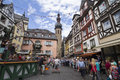 Cityscape of Cochem with its typical half-timbered houses and restaurants. Market square with town hall in background, people cele Royalty Free Stock Photo