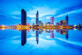 Cityscape in reflection of Ho Chi Minh city at beautiful twilight, viewed over Saigon river. Royalty Free Stock Photo