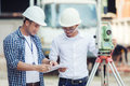 Civil Engineers At Construction Site and A land surveyor using a Royalty Free Stock Photo