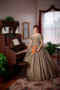 Civil war historical woman standing by pump organ an elegant dressed in a era ball gown stands a viintage with fan Stock Photo