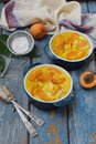 Clafouti with apricots in rameken on blue wooden background. Fruits clafoutis. Sweet casserole. Traditional French cake. Copy Royalty Free Stock Photo