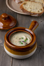 Clam chowder pot on weathered wood table vintage clay pots green pea squid meat scallops are visible in the creamy slices of Stock Photo