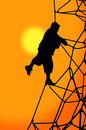 Clambering kid silhouette of boy on rope climbing frame at sunset Royalty Free Stock Photo