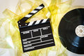 Clapper board with mm film yellow frames and movie reel empty unrolled cinema on neutral background Stock Photo