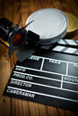 Clapper board with movie light and film reels on wooden table Royalty Free Stock Image