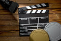 Clapper board with movie light and film reels on wooden table top view of Stock Image