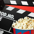 Clapper board and popcorn box on red background Royalty Free Stock Image