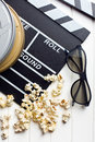 Clapperboard with d glasses and popcorn top view of on white wooden table Stock Photos