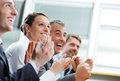 Clapping business people group of cheerful businesspeople sitting in a row on a presentation and Stock Image