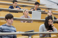 Class listening in a lecture hall students college and taking notes Royalty Free Stock Image