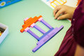 Classes in kindergarten baby gathered picture of different color sticks on the table Royalty Free Stock Image