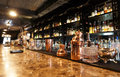 Classic bar counter with bottles in blurred background Stock Photography