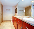 Classic bathroom with cherry cabinets brown two sinks view of bath tub corner Stock Image
