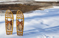 Classic bear paw snowshoes wooden on the shore of partially frozen cache la poudre river near fort collins colorado Royalty Free Stock Image