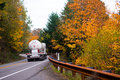 Classic big rig with propane tank on winding autumn road