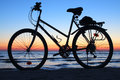 stock image of  Classic bike standing in the sand at sunset