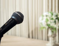 Classic black microphone on beautiful stage with brown curtain and big vintage style flowerpot in the corner close up of Royalty Free Stock Photography