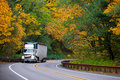Classic bonneted semi truck ribbed trailer on road autumn forest Royalty Free Stock Photo