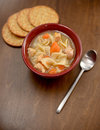 Classic bowl of chicken noodle soup with crackers Stock Photos