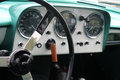 Classic british car vintage interior dials instruments switches shifter and steering wheel and dashboard in green and white Royalty Free Stock Photo