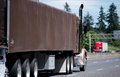 Classic brown semi truck tractor and brown semi trailer covered Royalty Free Stock Photo