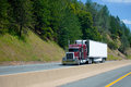 Classic burgundy big rig semi truck with reefer unit on refrigerator trailer going up on divided highway Royalty Free Stock Photo