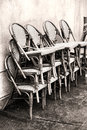 Classic cafe wicker chairs stacked against a wall bamboo seating with plastic weave cushions an old outside french bistro in Stock Photo