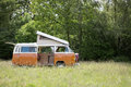 Classic camper van parked in a field ready for camping orange and set up with its doors open and covered wedding flowers and Stock Photography