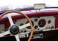 Classic car dashboard of an old with round measuring instruments and wooden steering wheel Royalty Free Stock Photo