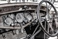 Classic car dashboard wooden with black driving wheel on the right hand side Royalty Free Stock Images