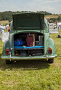 Classic car morris minor parked in a field with rear boot lid trunk lid open displaying its contents inside shopping bag cookies Royalty Free Stock Photography
