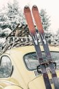 Classic car with vintage ski`s and sled during snowfall Royalty Free Stock Photo